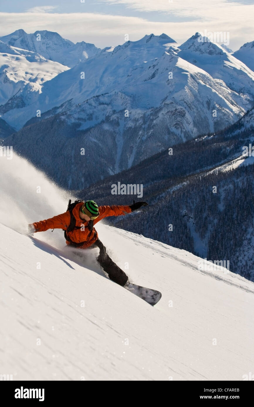 A snowboarder making turns at Rogers Pass, Glacier National Park, British Columbia, Canada - Stock Image
