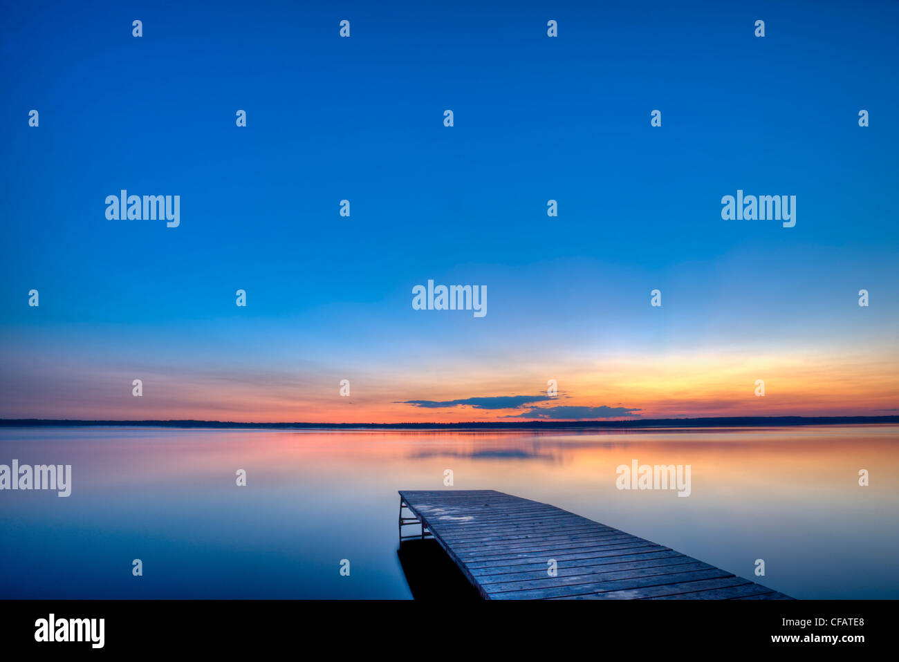 Sunset over a wooden wharf on Lake Audy, Riding Mountain National Park, Manitoba, Canada - Stock Image