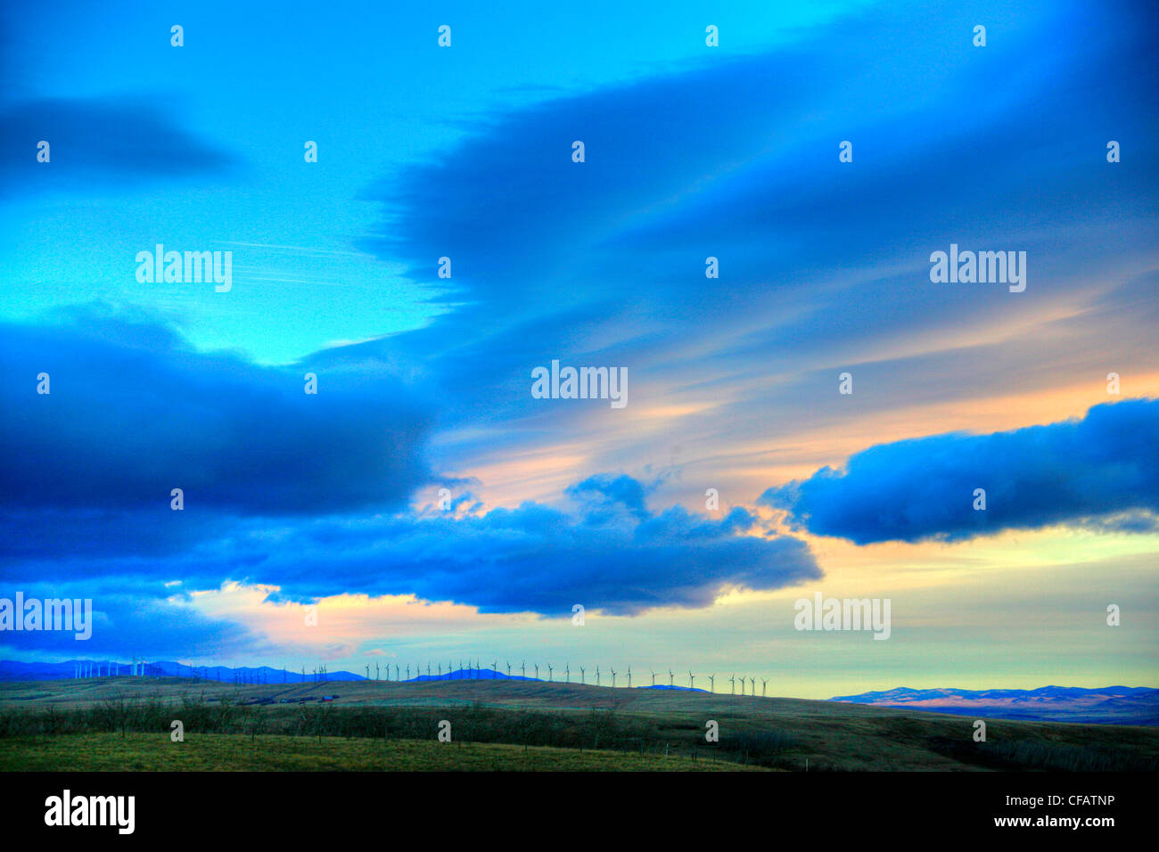 Wind farm with chinook clouds over top of them near Pincher Creek, Alberta, Canada - Stock Image