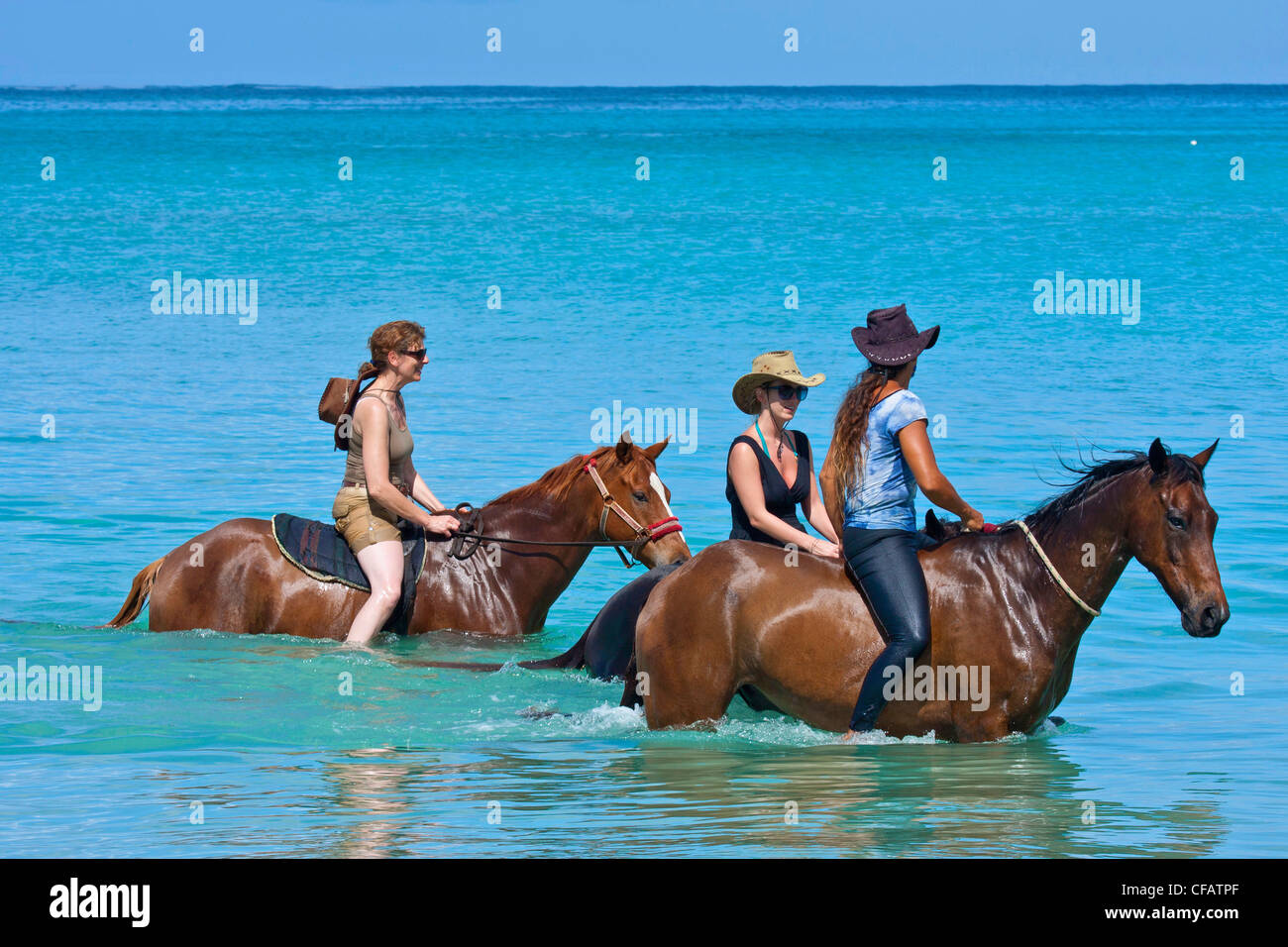 View of Buccoo Bay, Tobago with horse-riders in sea Stock Photo
