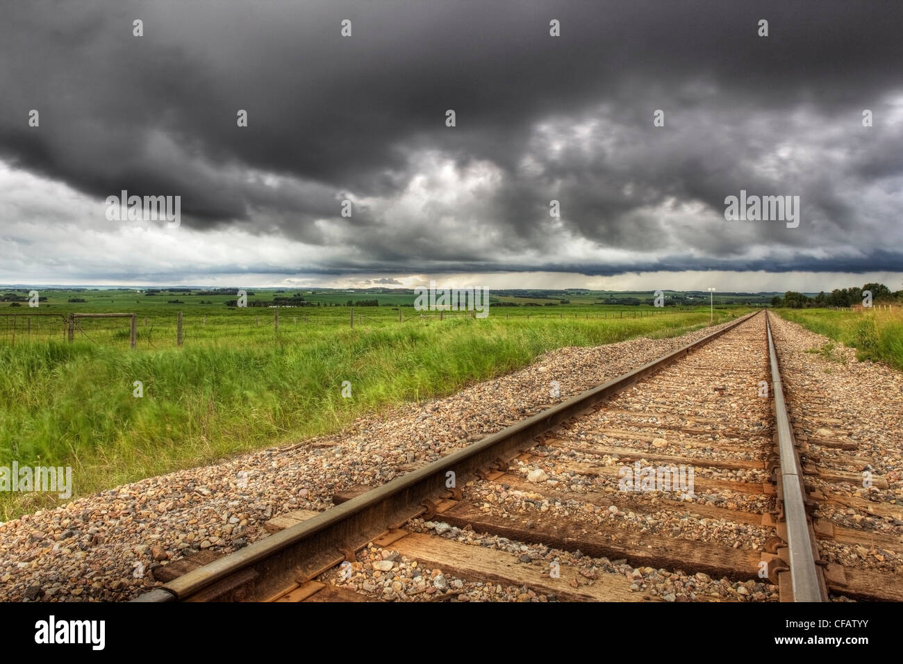 Railroad tracks with storm clouds in the background near Didsbury, Alberta, Canada - Stock Image