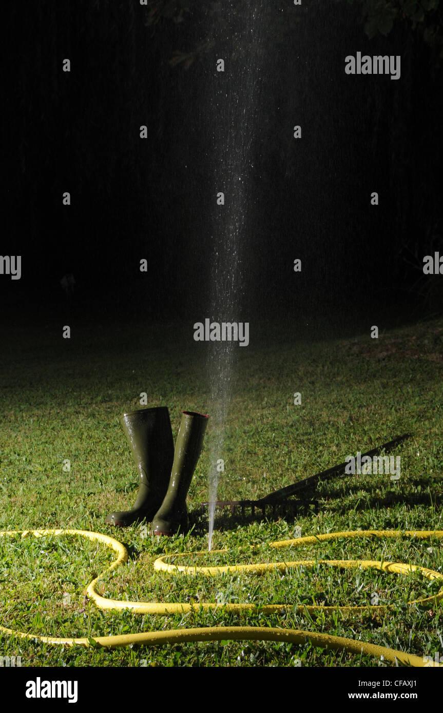 Garden, tube, water hose, lawn, watering, hole, splash, boot - Stock Image
