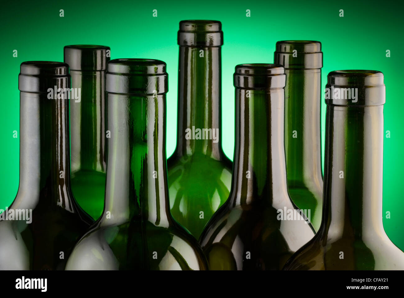 Wine bottle necks back lit on green Stock Photo
