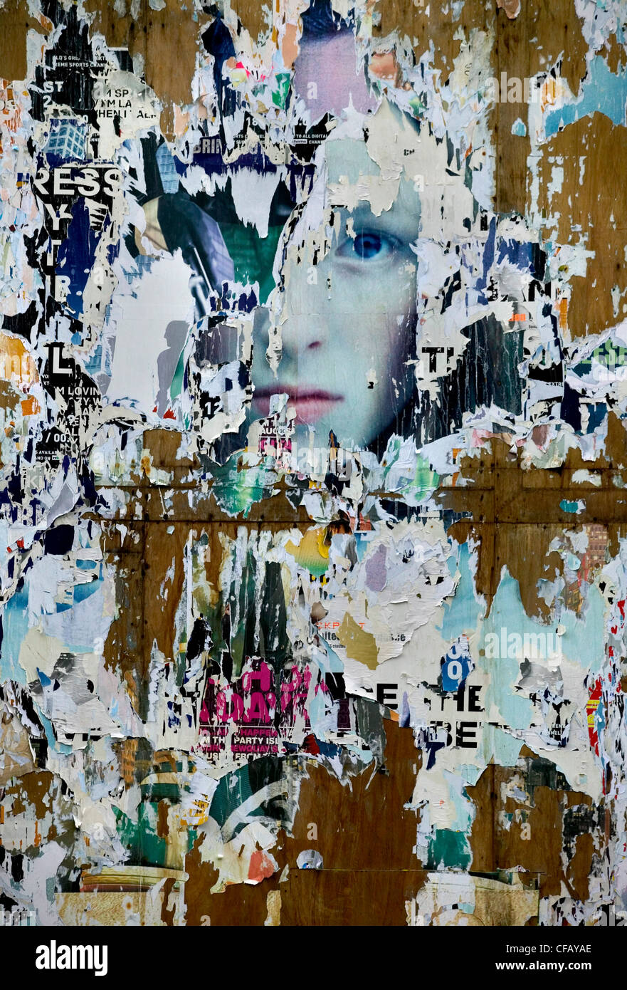 Torn poster with woman's face, London, UK. - Stock Image