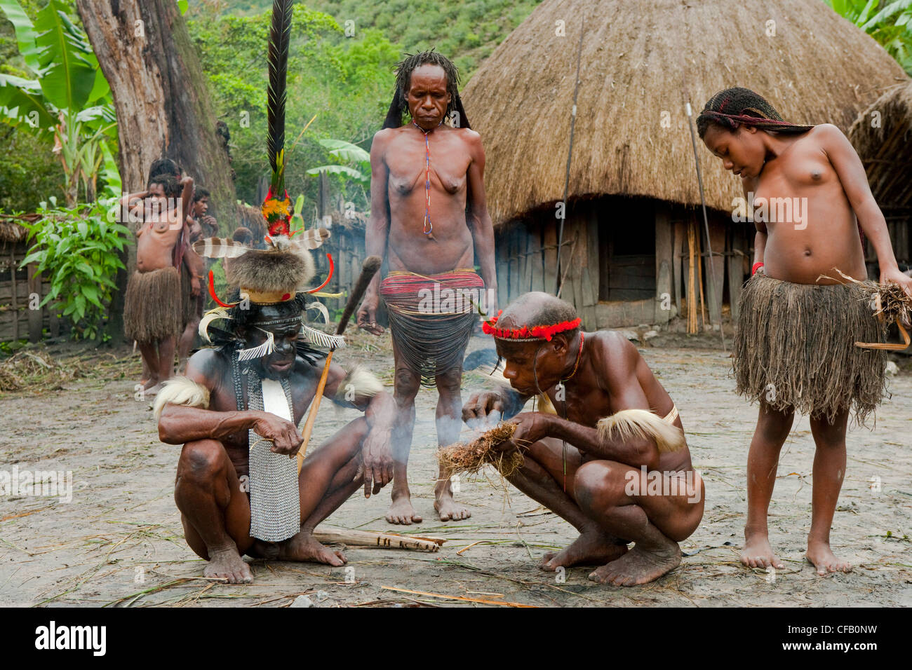 Dani tribespeople making fire in their traditional village, New Guinea, Indonesia. - Stock Image