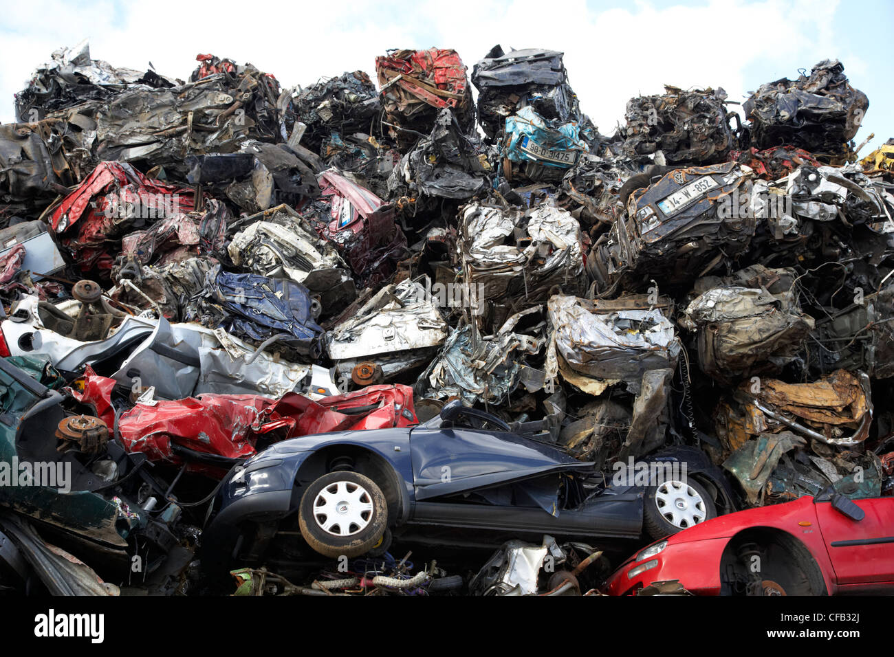 piles of crushed scrapped cars at metal recycling site Belfast Northern Ireland UK - Stock Image