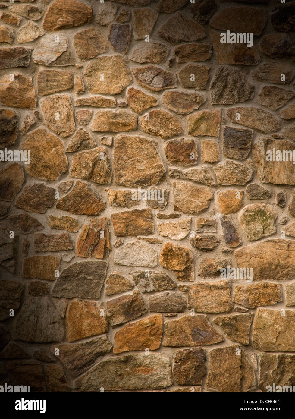 Brown masonry rock wall lit diagonally - Stock Image