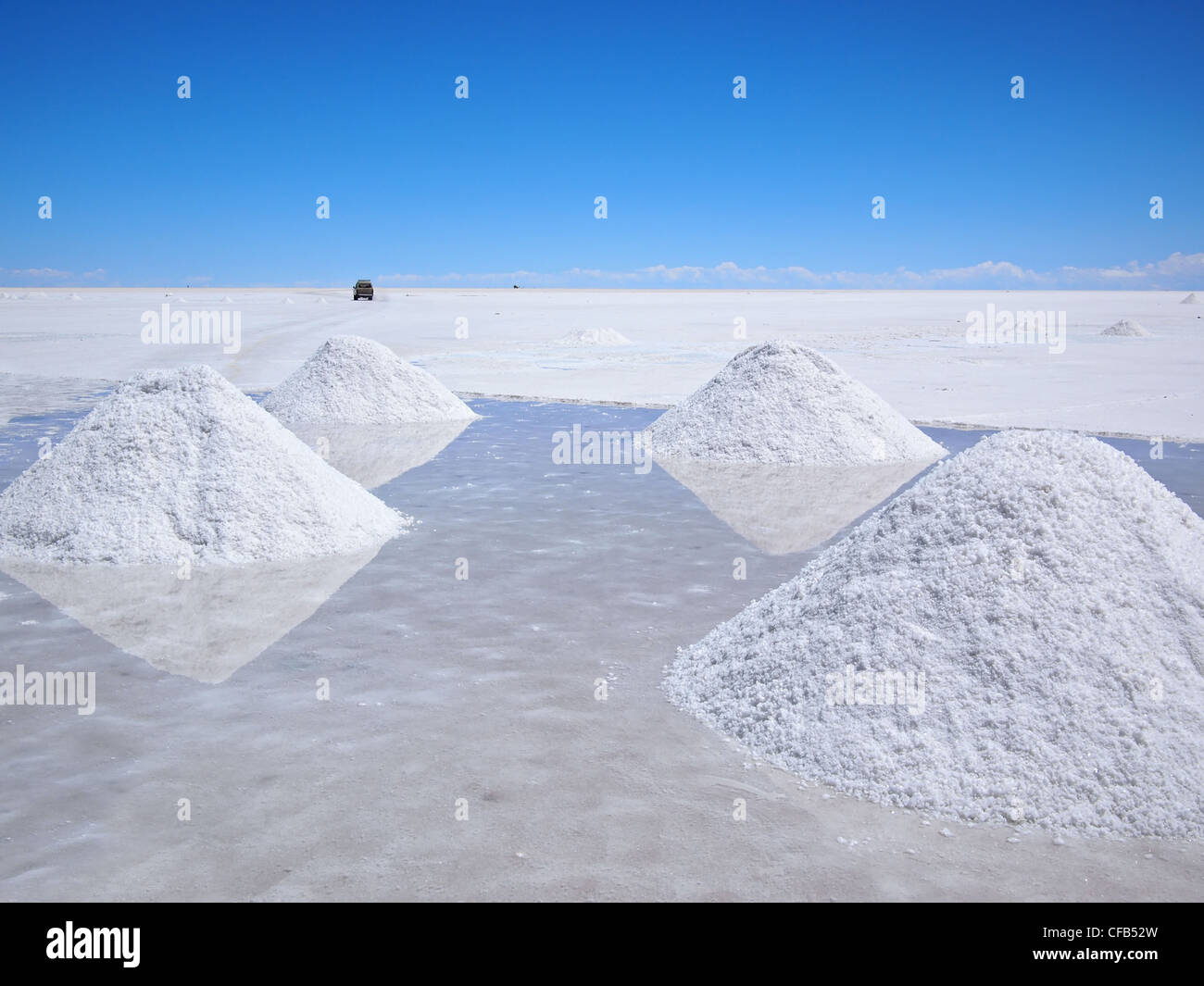 Piles of drying salt and reflection in the water at the Salar de Uyuni (salt flats) in Bolivia. - Stock Image