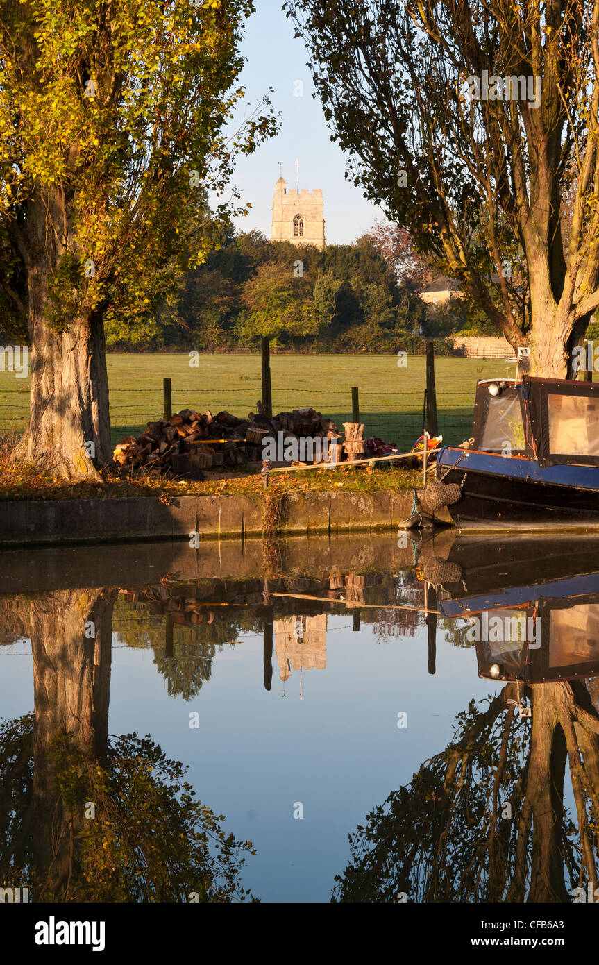View of Cosgrove church seen between Poplar trees and across the Grand Union canal. Northamptonshire,England, UK. - Stock Image