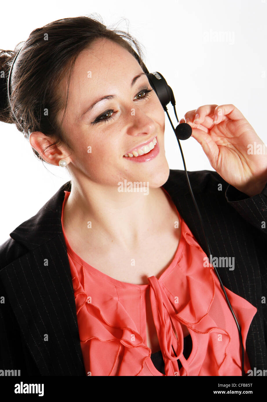 Attractive woman talks on her headset - Stock Image