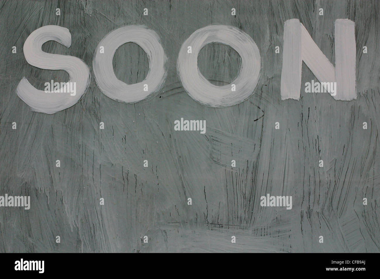 Whitewashed window with the word 'SOON' written on it - Stock Image