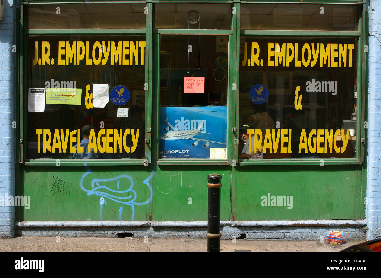 Windows of a disused, empty employment and travel agency, with poster of airplane in the doorway - Stock Image