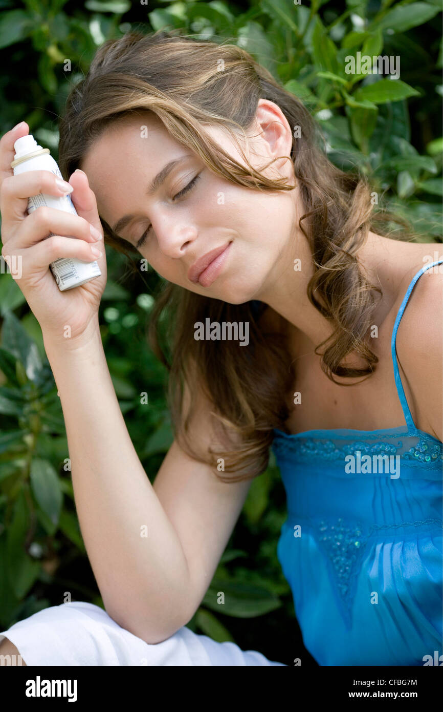 A DayYourself: Female long brunette hair tied back loosely wearing blue top holding small atomiser spray leaning - Stock Image