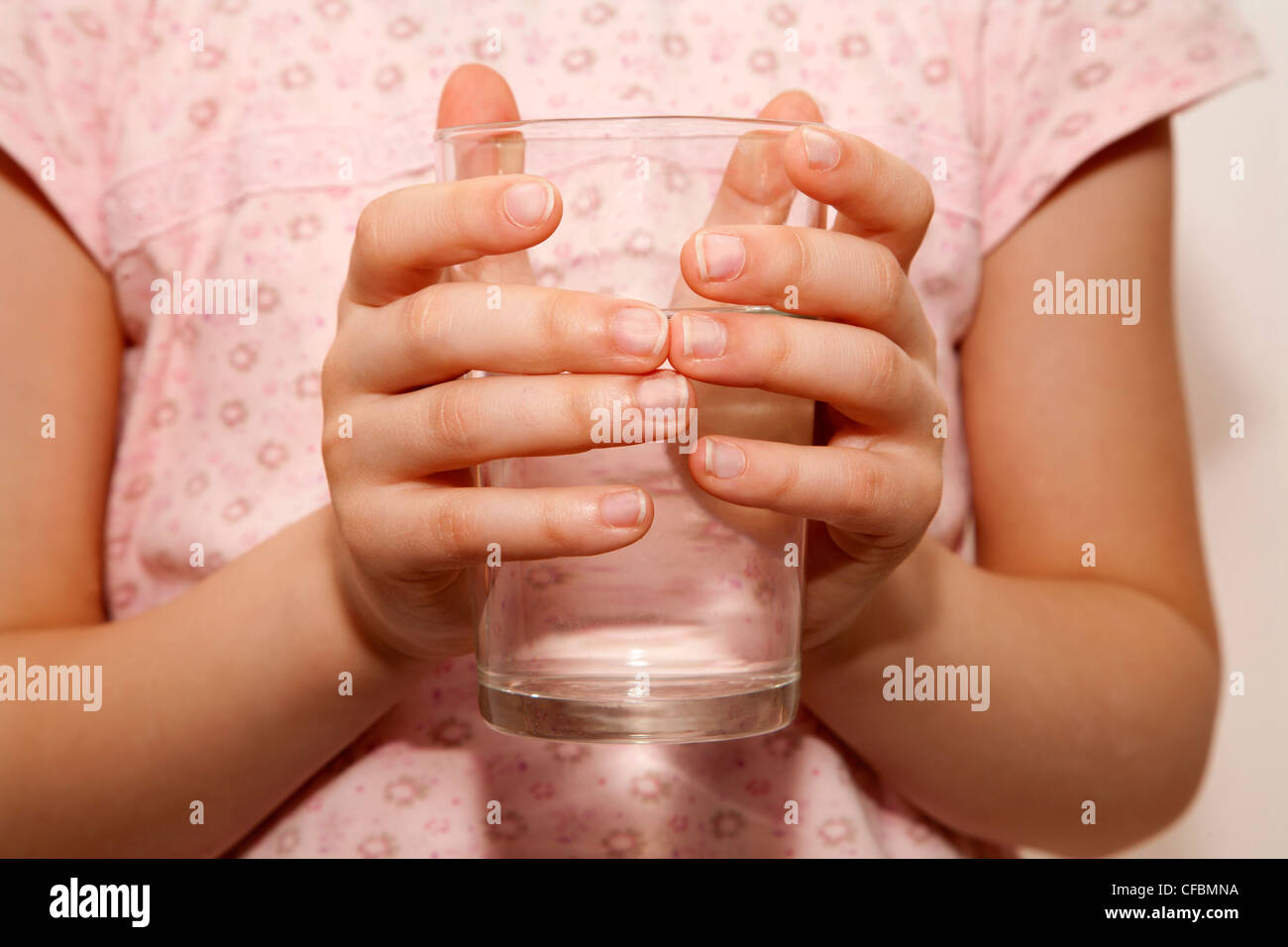 hands of little girl and glass of water - Stock Image