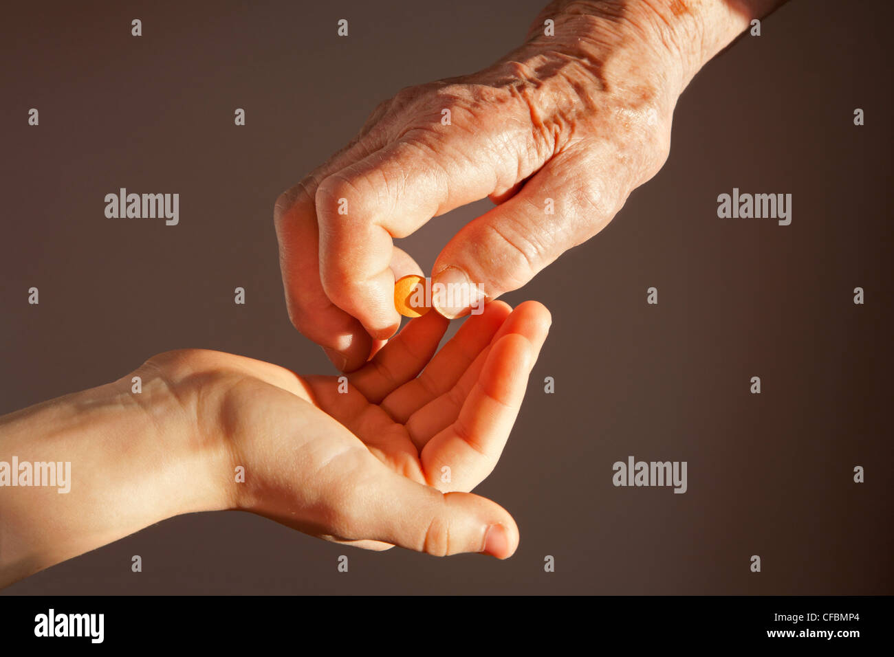 hand of grandmother and grandchild with a pill - Stock Image