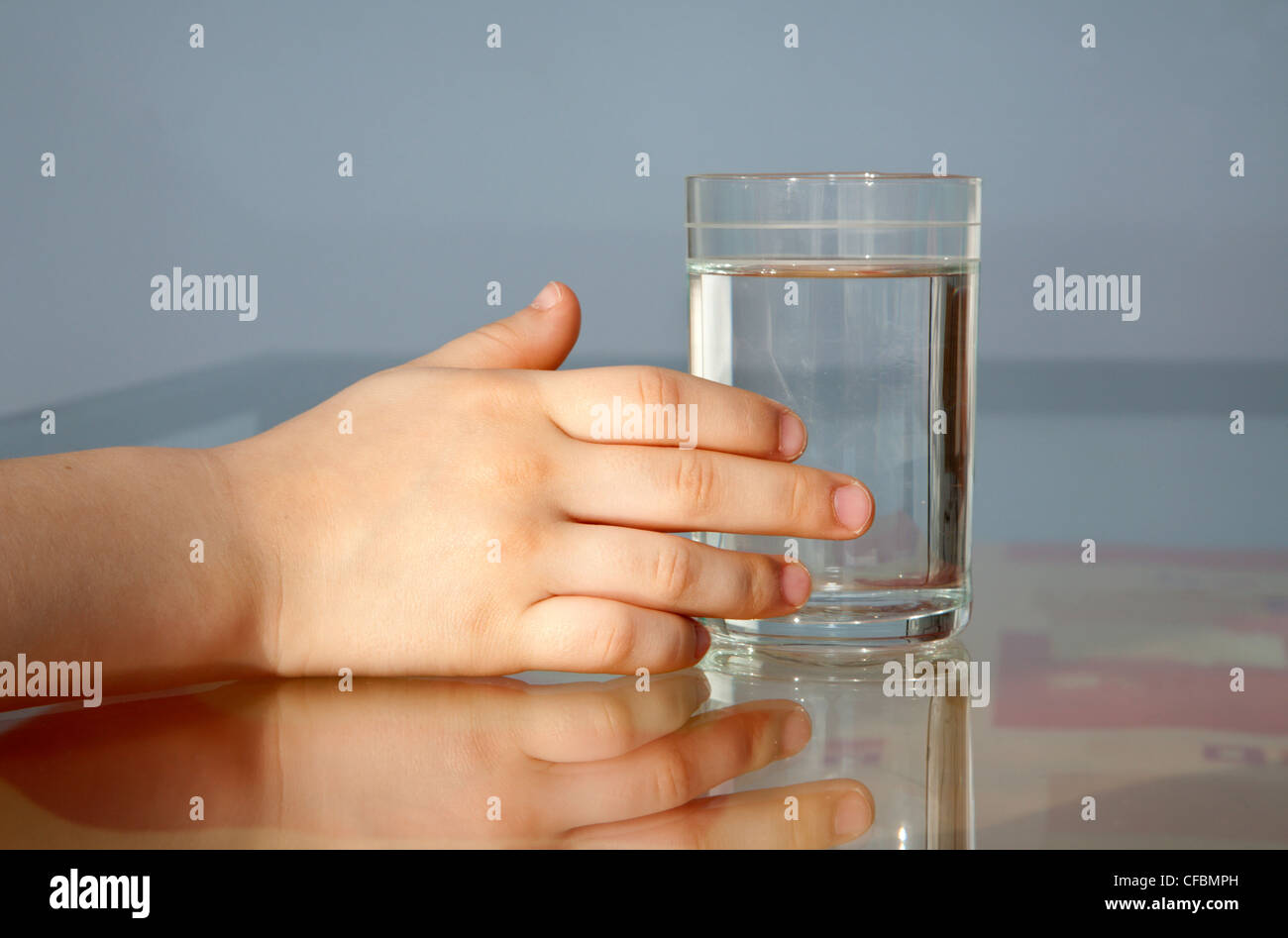 hand of child and glass of water - Stock Image