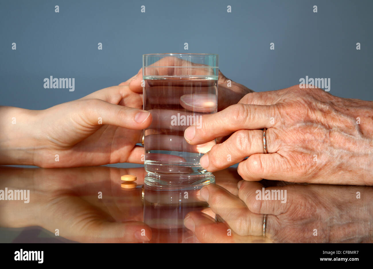hand of grandmother and women with a pill - Stock Image