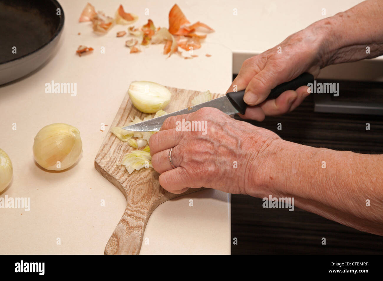 hands of old woman at cutting of bulb - Stock Image