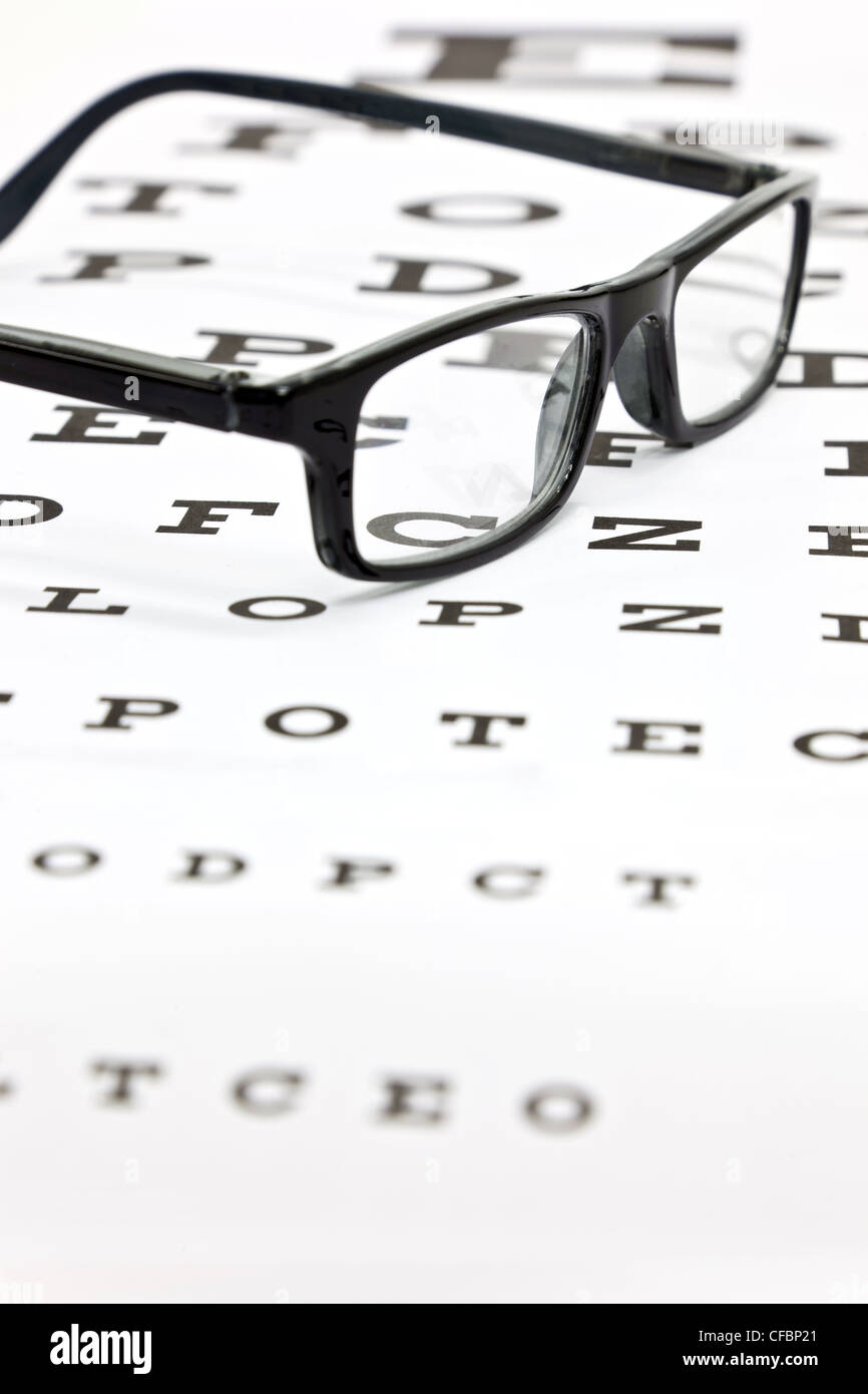 Photo of black spectacles on an eye test chart - Stock Image