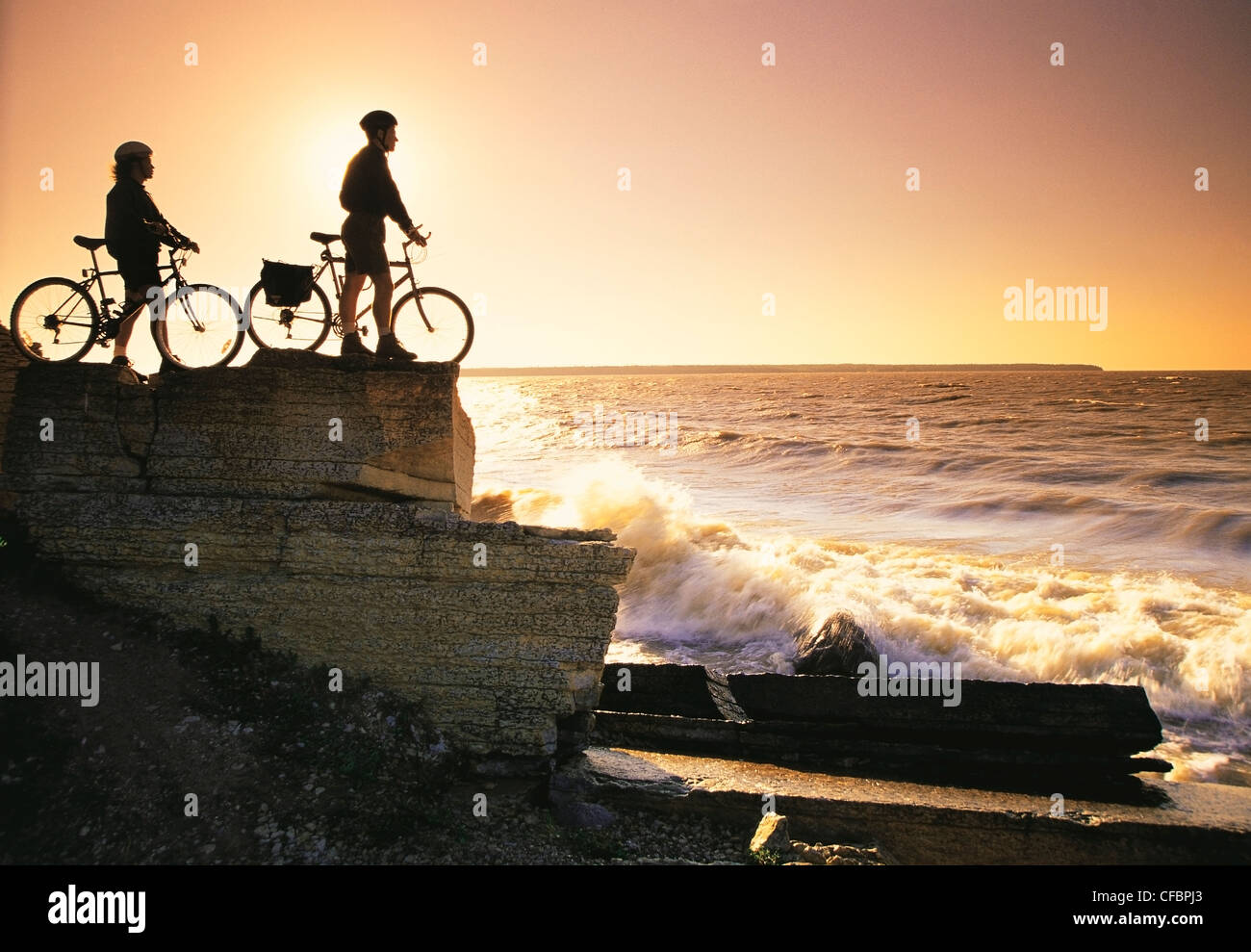 Cyclists along sedimentary rock cliffs, Hecla Provincial Park, Lake Winnipeg, Manitoba, Canada - Stock Image