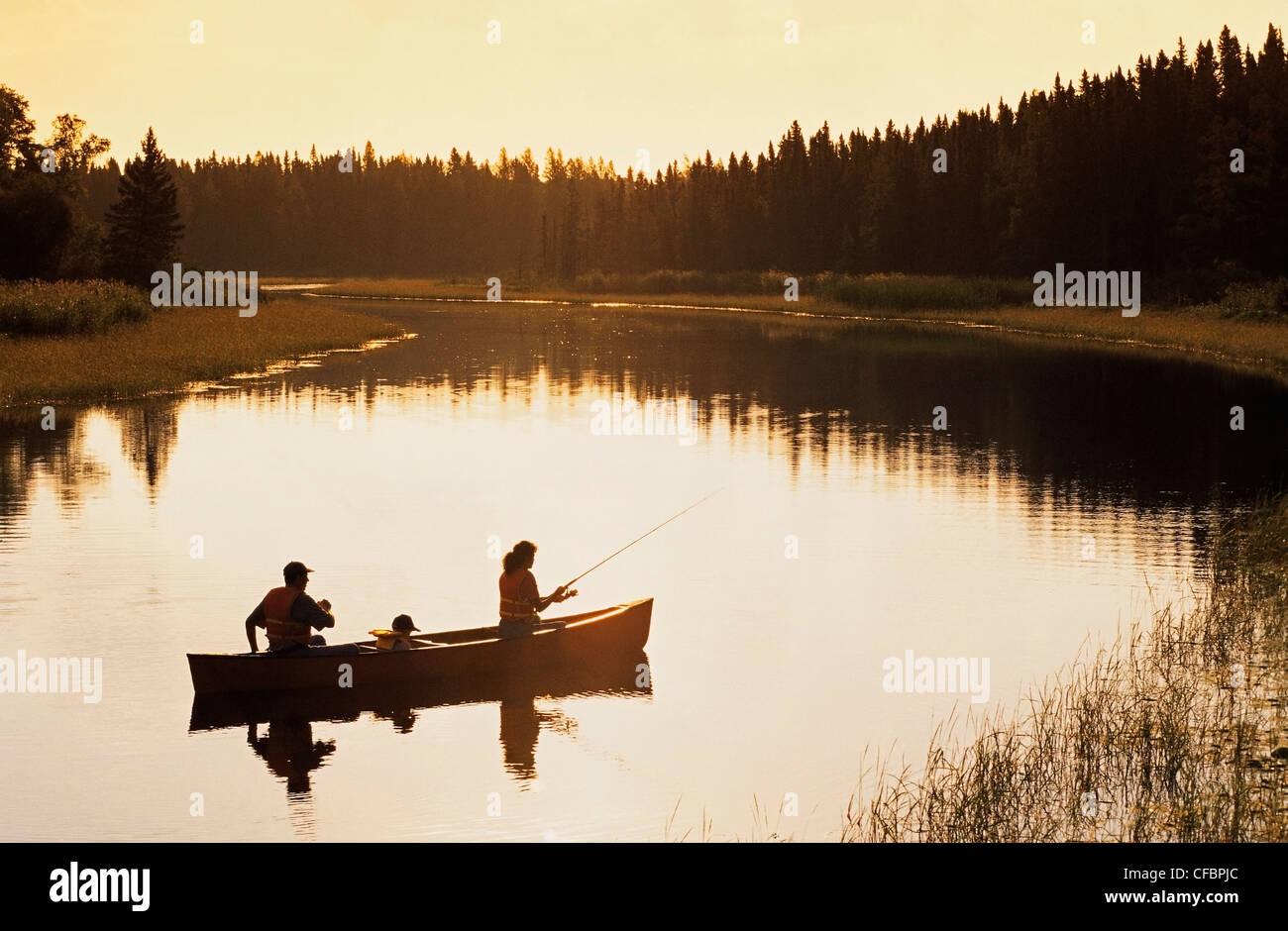 Family canoeing and fishing, Whiteshell River, Whiteshell Provincial Park, Manitoba, Canada - Stock Image