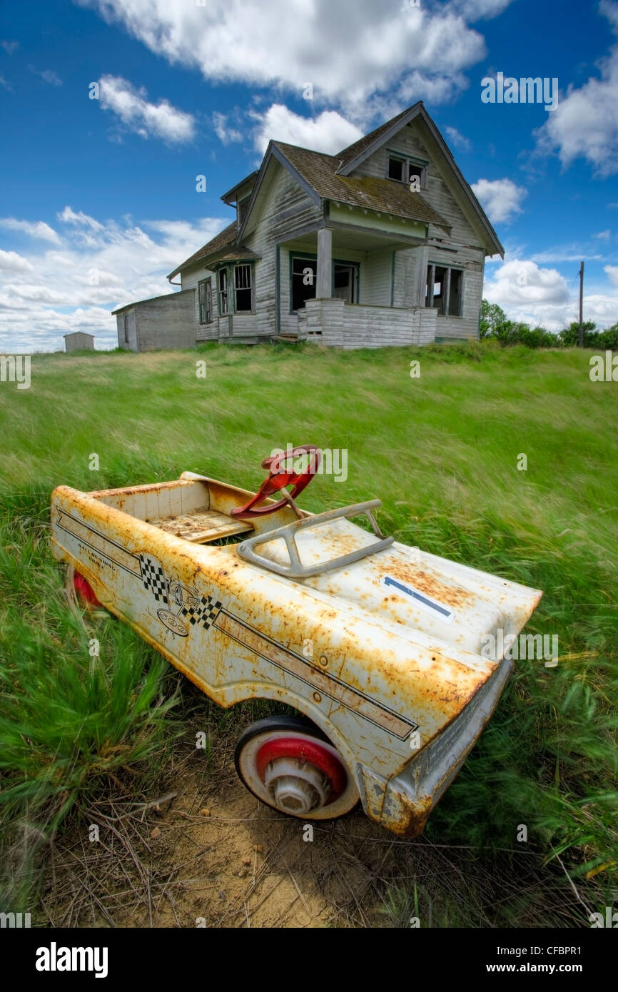 Abandoned farmhouse with child's pedal car, Saskatchewan, Canada - Stock Image