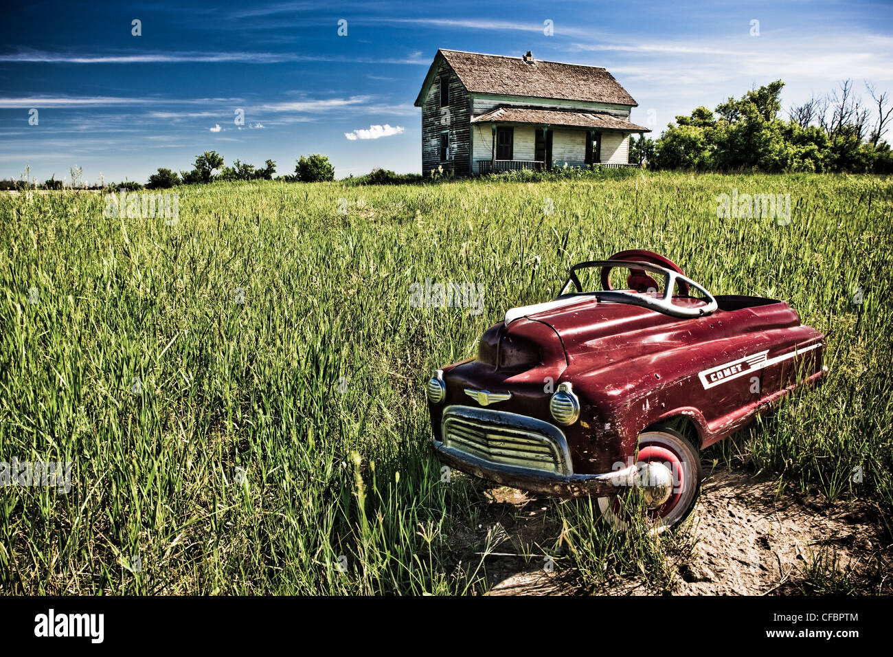 Child's pedal car and abandoned homestead near Camrose, Alberta, Canada - Stock Image