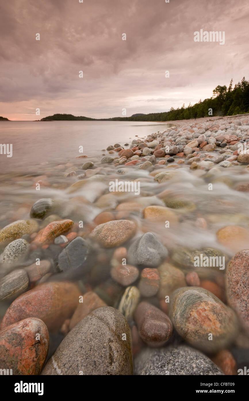Small stream running boulders rocky shore - Stock Image