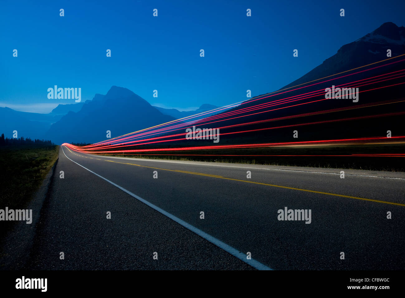 passing vehicle leaves light trails along - Stock Image