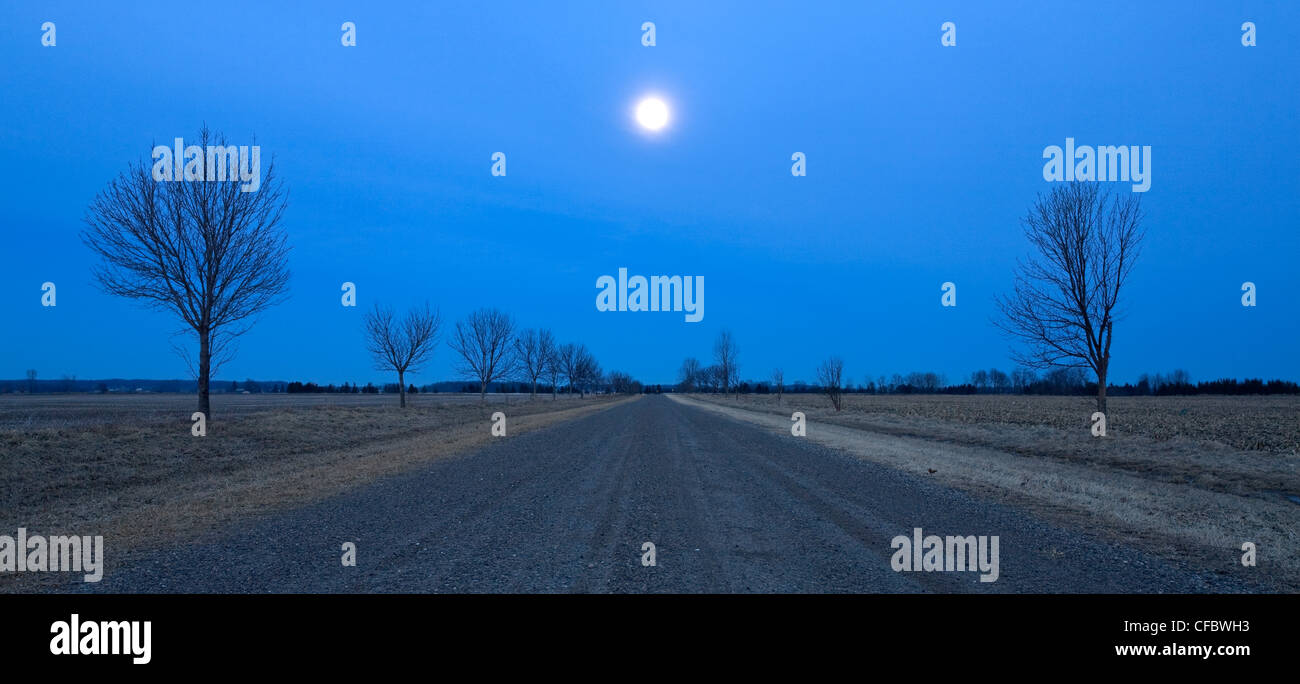 The moon rises over this country road near Grand Bend, Ontario, Canada - Stock Image
