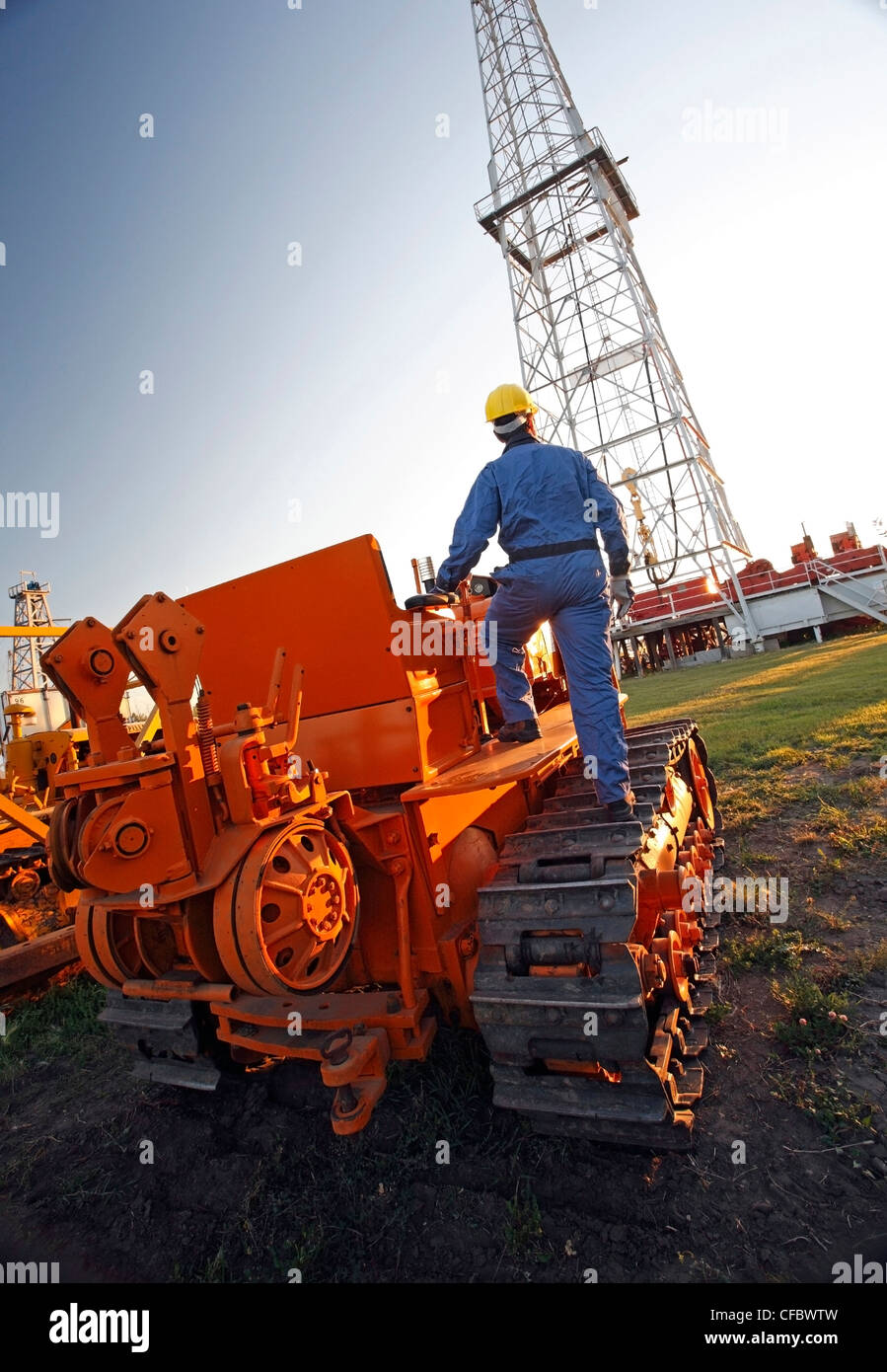Worker on earth moving equipment at oil drilling site - Stock Image