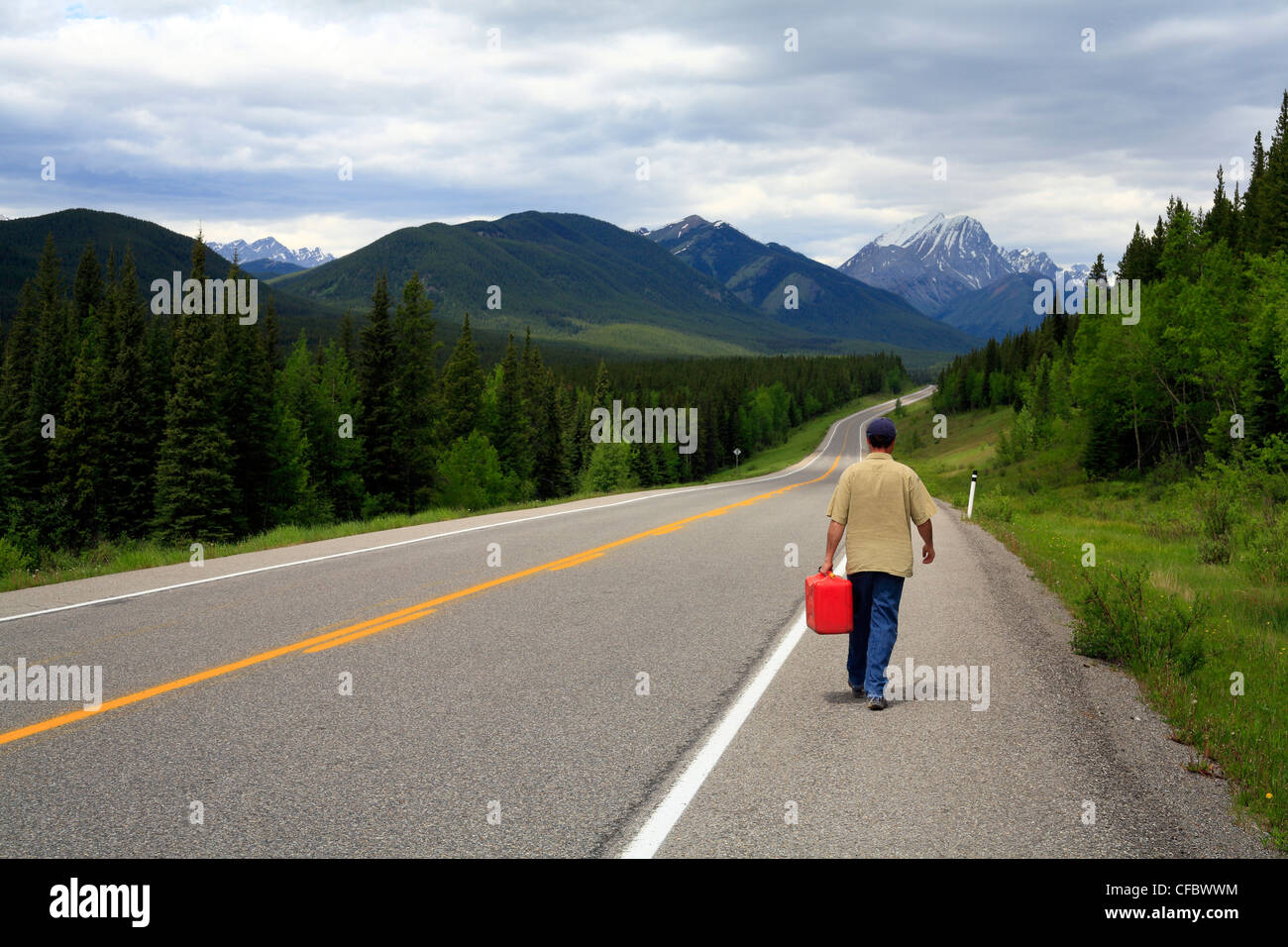 Driver walking with gas can on mountain highway, Kananaskis Provincial Park, Alberta, Canada - Stock Image