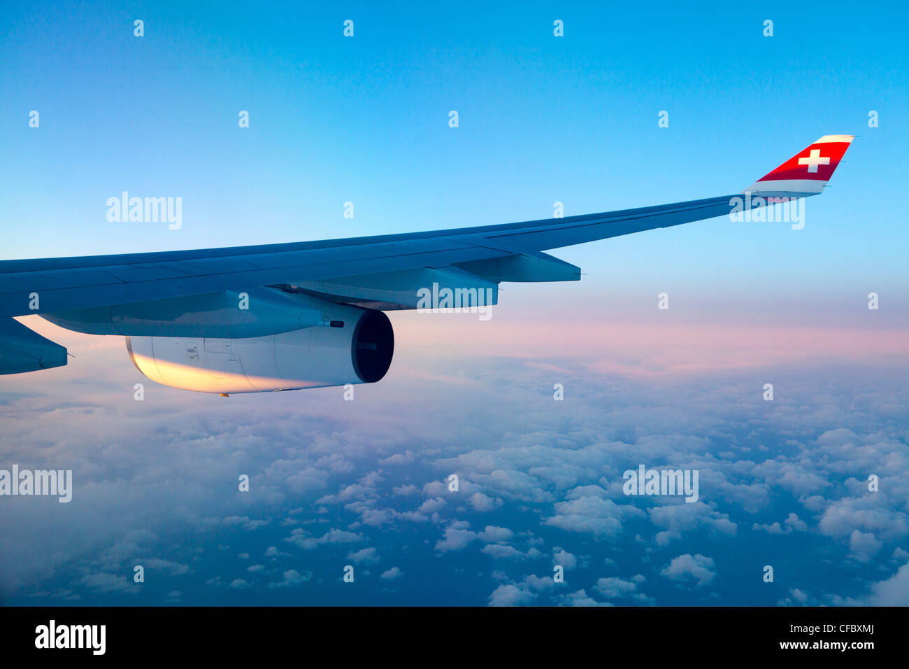 airplane, Swiss, wing, sunset, clouds, cross, engine, flight, fly, engine, plane, sunset, travel, wing, concepts - Stock Image