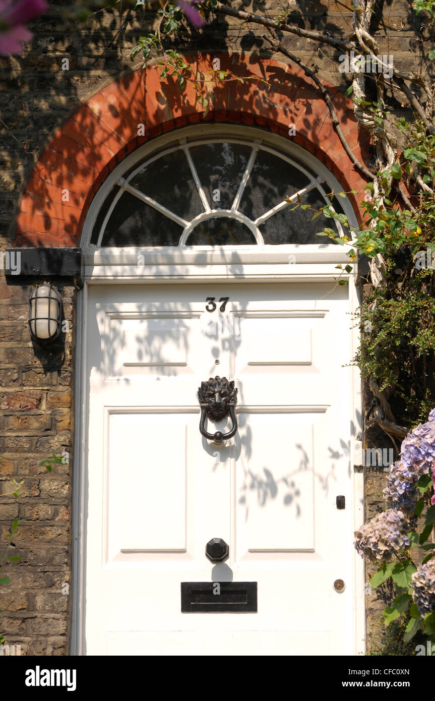 White front dowith black lion head shaped knocker, letterbox and knob, semi circle arch window above dowith red - Stock Image