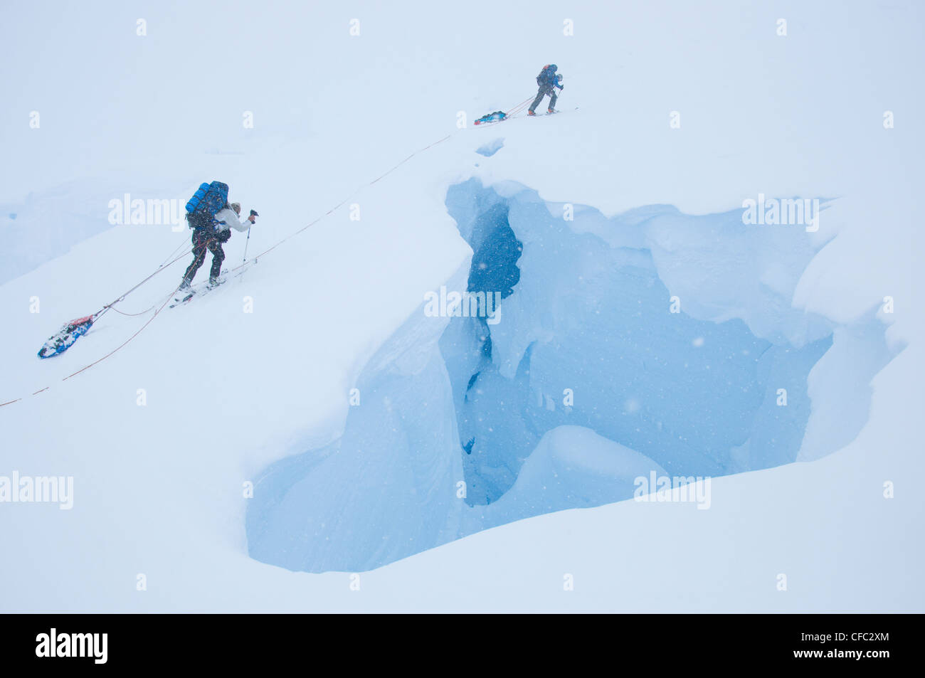 Two skiers on an extended ski traverse cross a gaping crevasse in the remote Darwin Range, southern Chile - Stock Image