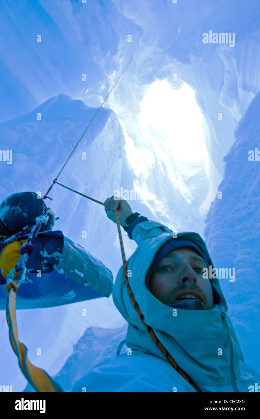 A skier who fell down a crevasse while travelling on a glacier in the Darwin Range, Chile, is in a tricky situation - Stock Image