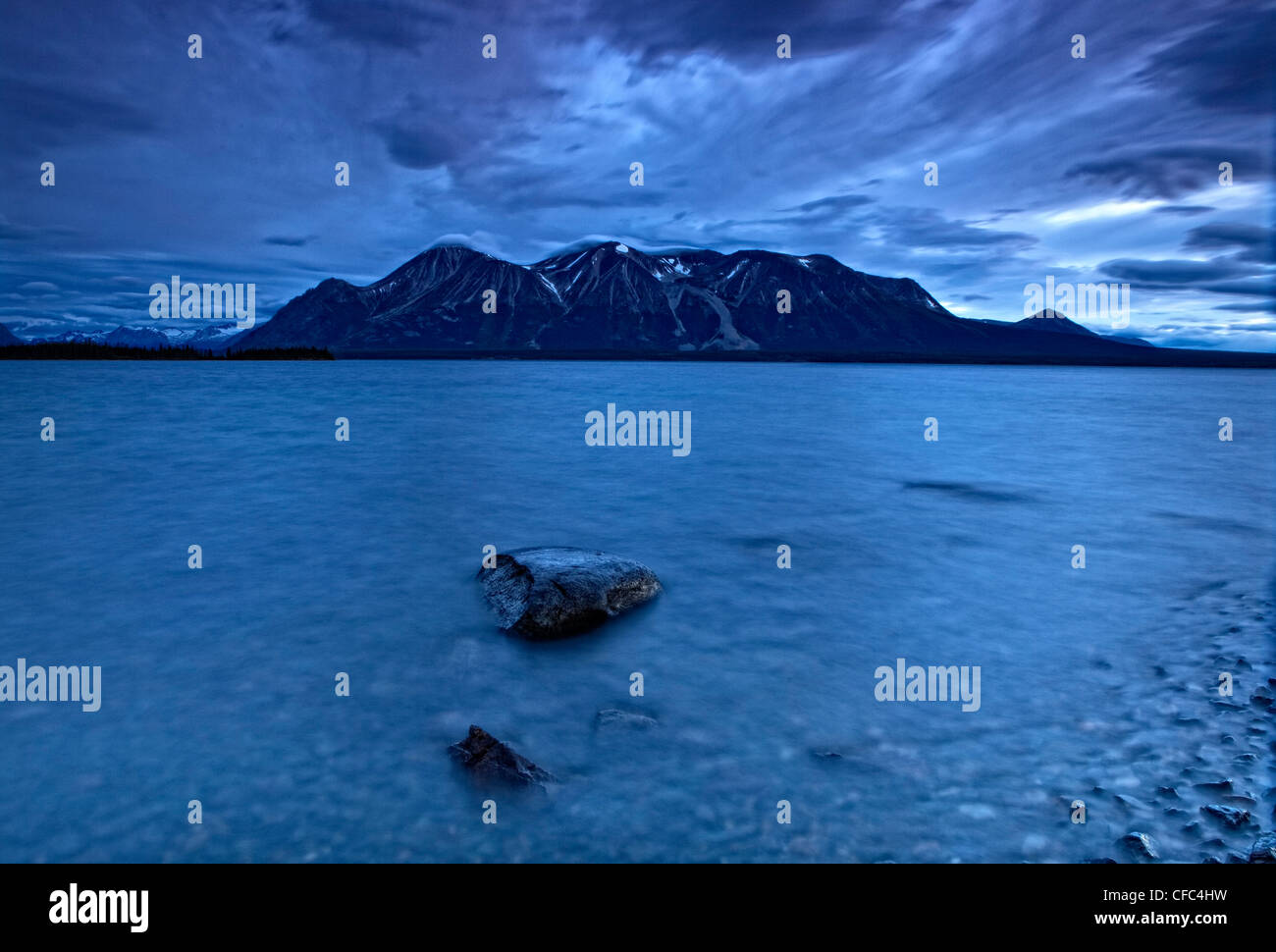 Long exposure of Teresa Mountain and Atlin Lake taken from the shore after sunset. Located in northern British Columbia - Stock Image