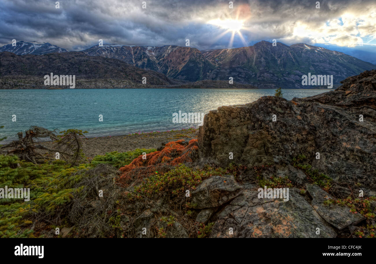 HDR image of setting sun over Atlin Lake, BC. Taken from Sloco Island in Atlin Provincial Park, Atlin, British Columbia, - Stock Image