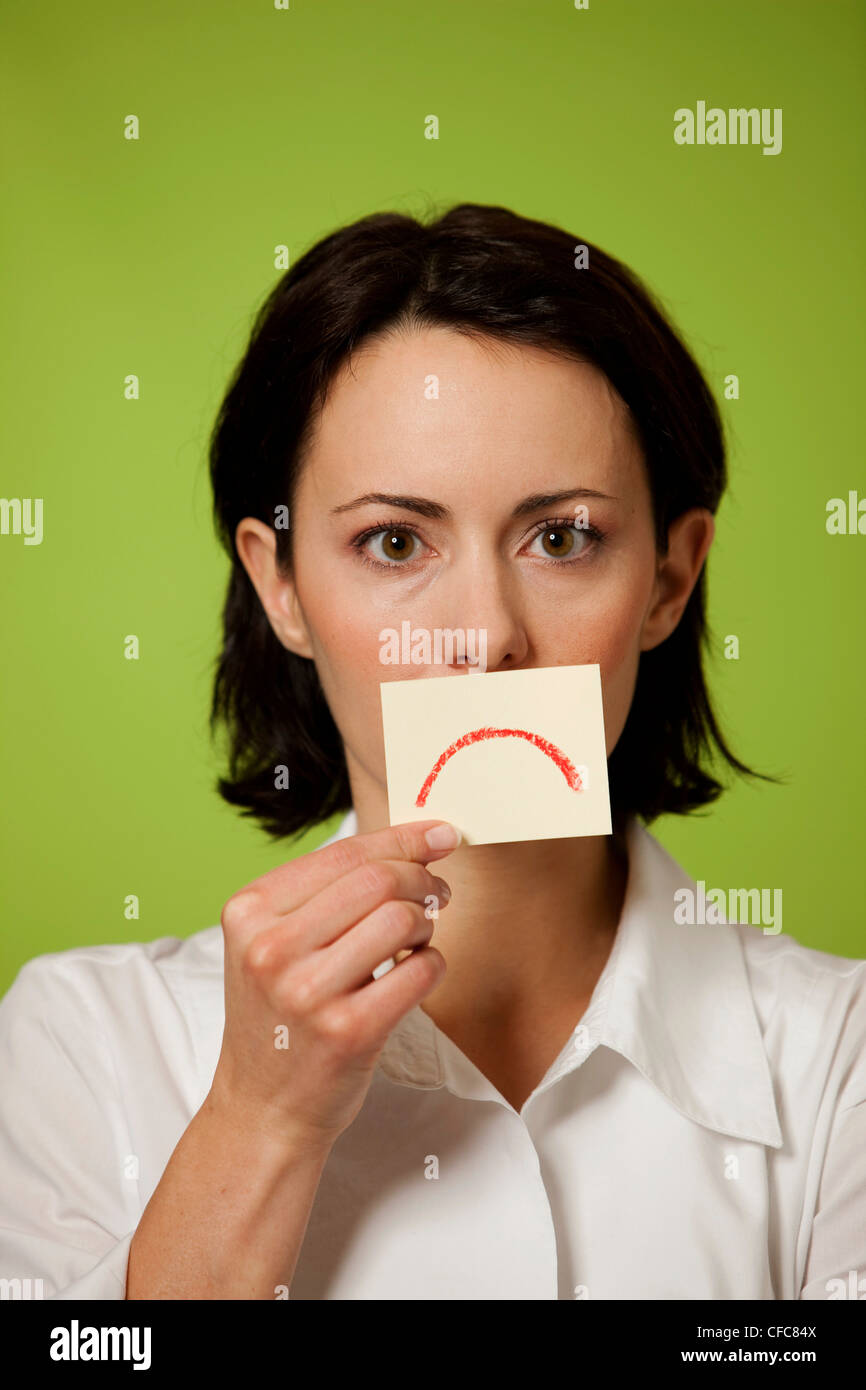 Mid adult woman holding postit note - Stock Image