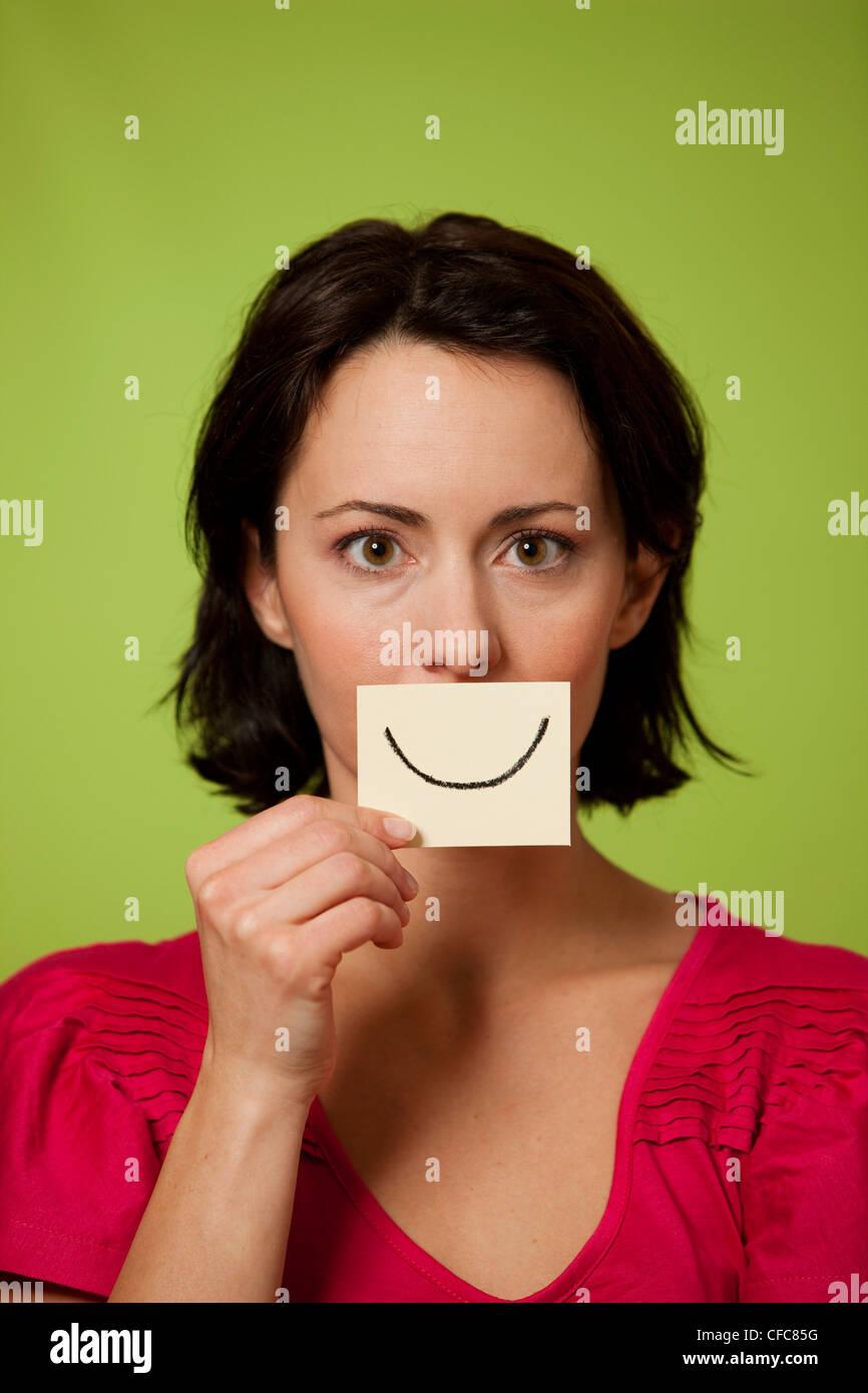 Mid audlt woman holding smiling postit note - Stock Image