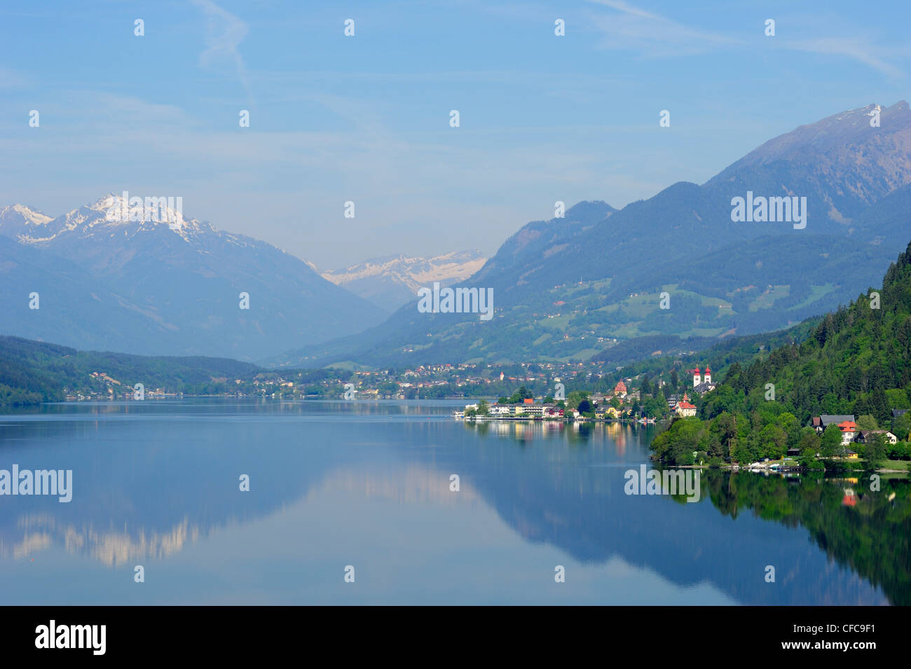 Lake Millstaetter See with convent Millstatt and snow covered mountains in the background, lake Millstaetter See, - Stock Image