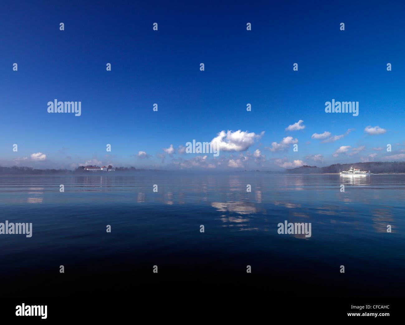 View across the reflecting lake towards Herreninsel, ferry boat, Lake Chiemsee, Chiemgau, Bavaria, Germany Stock Photo
