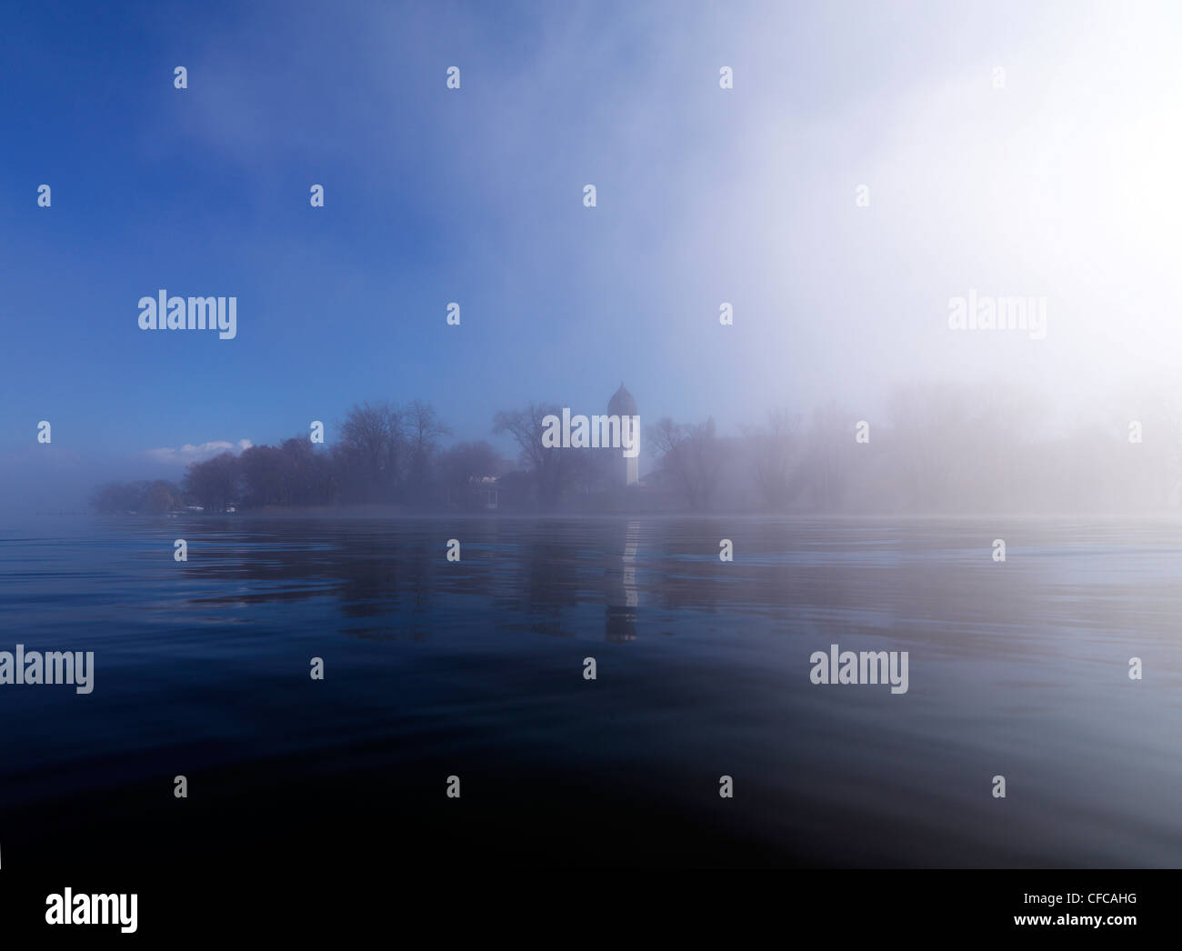 Misty scenery with tower of Frauenwoerth monastery in the background, Frauenchiemsee, Fraueninsel, Chiemgau, Bavaria, Stock Photo