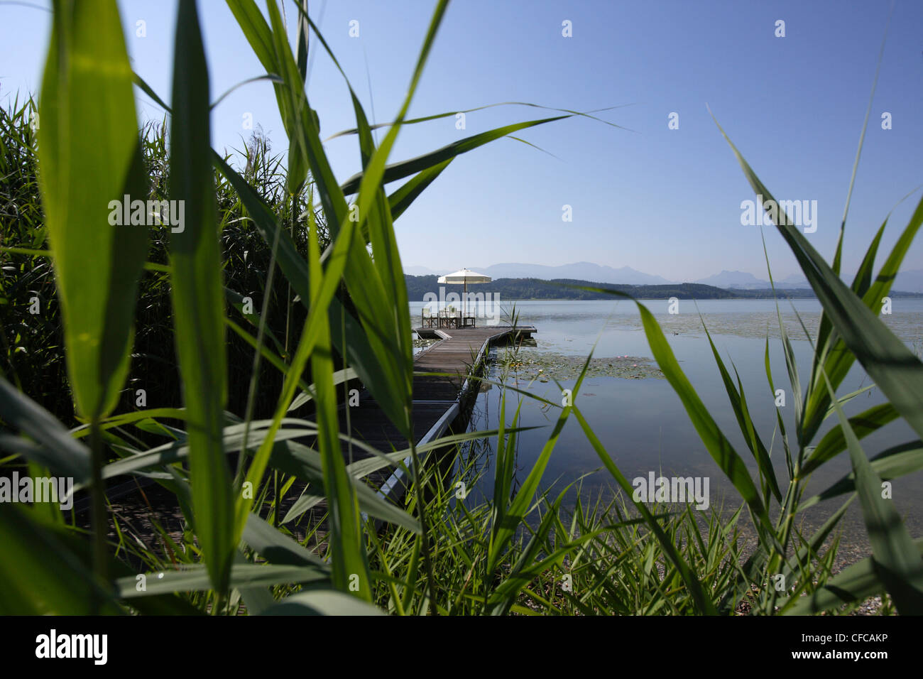 Sunshade on a wooden jetty, Simssee, Bavaria, Germany - Stock Image