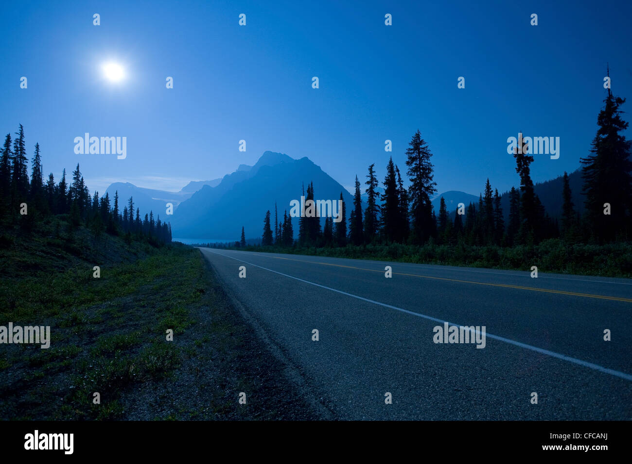 full moon lights Icefields Parkway leads Crowfoot - Stock Image