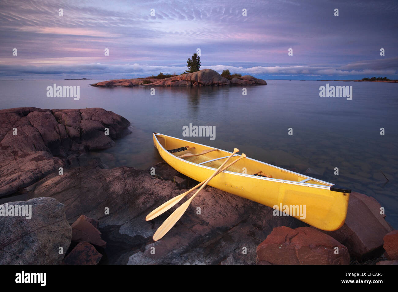 Canoe by granite islands of Georgian Bay, Killarney Provincial Park, Ontario - Stock Image