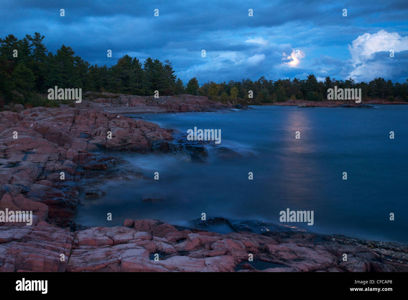 A full moon is unveiled as clouds pass over Georgian Bay in Killarney Provincial Park in Northern Ontario. - Stock Image