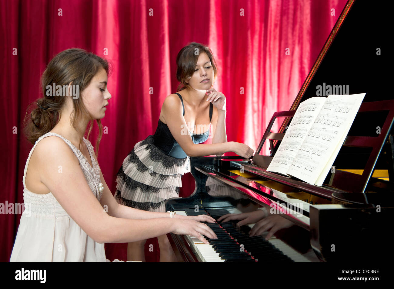 Duet with vocals and piano, performed by two young women on stage - Stock Image