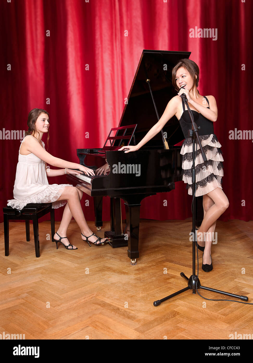 Duet with a young pianist behind a grand piano, looking at a beautiful lead singer - Stock Image