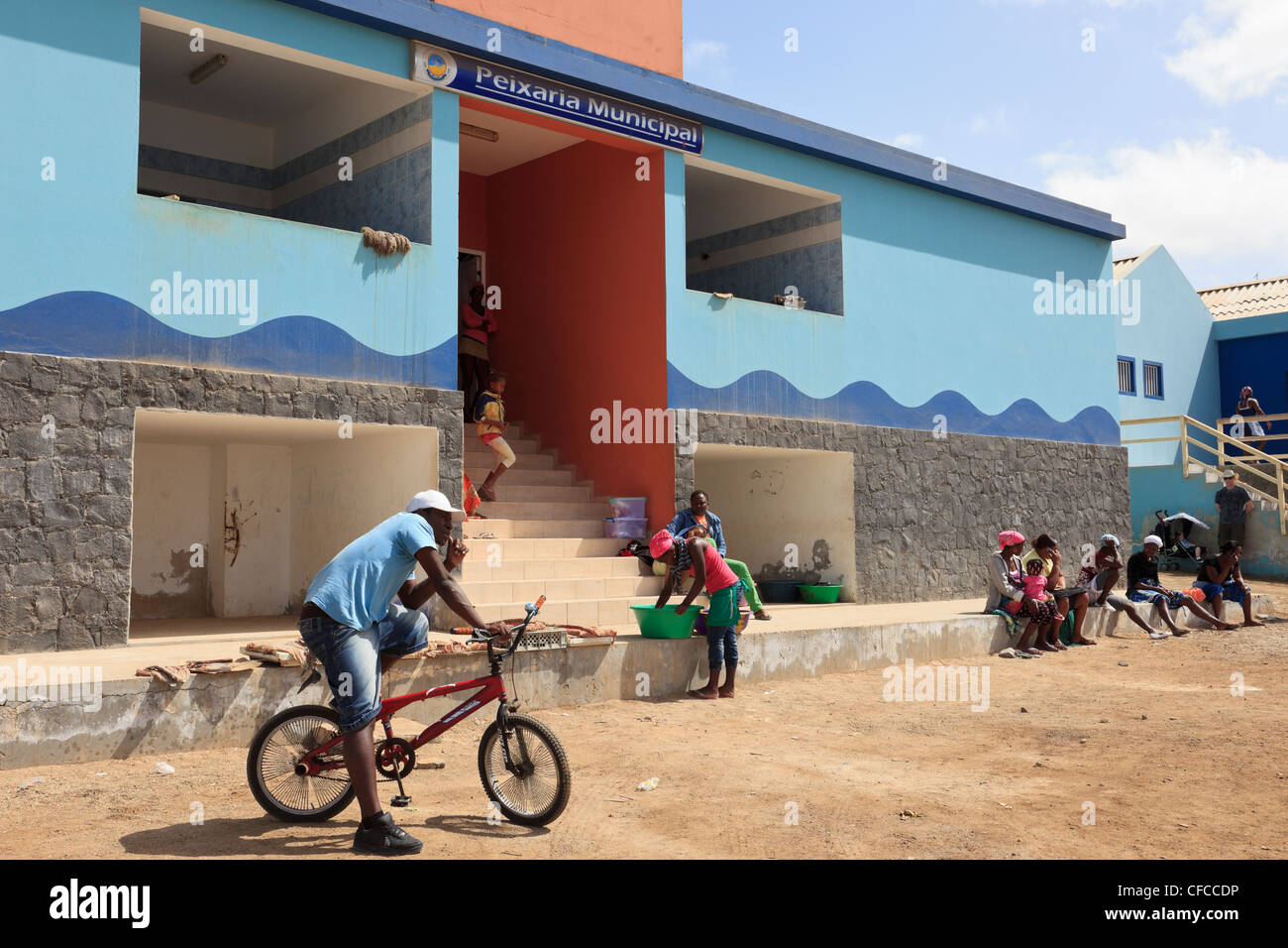 Sal Rei, Boa Vista, Cape Verde Islands. Port scene with local people sitting outside the new municipal fish market. - Stock Image